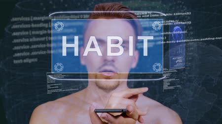 cite : Young man interacts with a conceptual HUD hologram with text Habit. Guy with future technology mobile screen on background of the program code Stock Footage