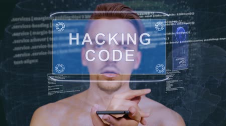 botok : Young man interacts with a conceptual HUD hologram with text Hacking code. Guy with future technology mobile screen on background of the program code