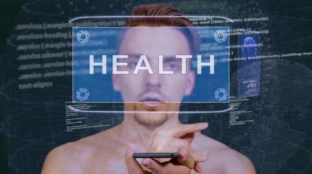 identificare : Young man interacts with a conceptual HUD hologram with text Health. Guy with future technology mobile screen on background of the program code Filmati Stock
