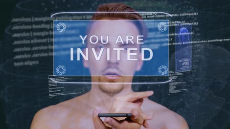 felkiáltás : Young man interacts with a conceptual HUD hologram with text You are invited. Guy with future technology mobile screen on background of the program code