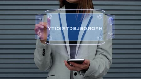 hidro : Unrecognizable business woman, interacts with HUD hologram with text Hydroelectricity. Girl in a business suit uses the technology of the future mobile screen against the background of a striped wall