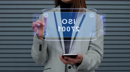 iso : Unrecognizable business woman, interacts with a HUD hologram with text ISO 27001. Girl in a business suit uses the technology of the future mobile screen against the background of a striped wall