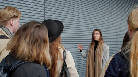 темы : A beautiful young female team leader of young people tells the projects strategy against the backdrop of a modern striped wall. Young people talking about serious topics