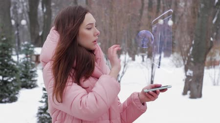 микрочип : Beautiful young woman in a winter park interacts with HUD hologram computer processor. Red-haired girl in warm pink clothes uses the technology of the future mobile screen