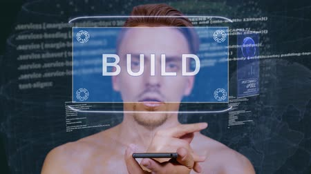 interacts : Young man interacts with a conceptual HUD hologram with text Build. Guy with future technology mobile screen on background of the program code Stock Footage
