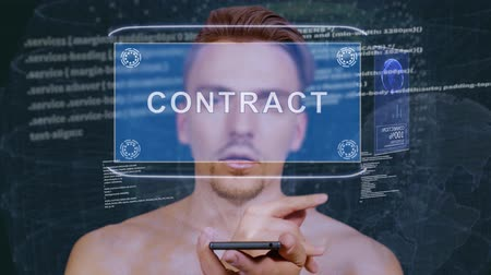 implementation : Young man interacts with a conceptual HUD hologram with text Contract. Guy with future technology mobile screen on background of the program code Stock Footage