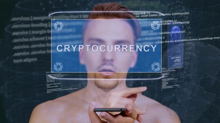 стратегический : Young man interacts with a conceptual HUD hologram with text Cryptocurrency exchange. Guy with future technology mobile screen on background of the program code Стоковые видеозаписи