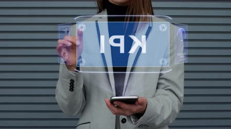 uygulanması : Unrecognizable business woman, interacts with a HUD hologram with text KPI. Girl in a business suit uses the technology of the future mobile screen against the background of a striped wall