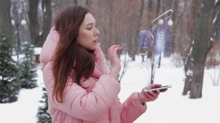 sell : Beautiful young woman in a winter park interacts with HUD hologram stacks of money. Red-haired girl in warm pink clothes uses the technology of the future mobile screen