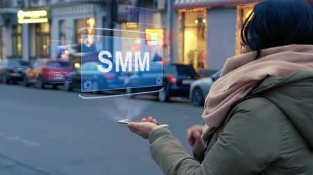 hodnost : Unrecognizable woman standing on the street interacts HUD hologram with text SMM. Girl in warm clothes uses technology of the future mobile screen on background of night city