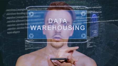 optimalizace : Young man interacts with a conceptual HUD hologram with text Data Warehousing. Guy with future technology mobile screen on background of the program code
