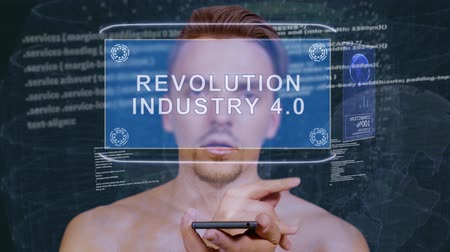 quantum computer : Young man interacts with a conceptual HUD hologram with text Revolution Industry 4.0. Guy with future technology mobile screen on background of the program code Stock Footage