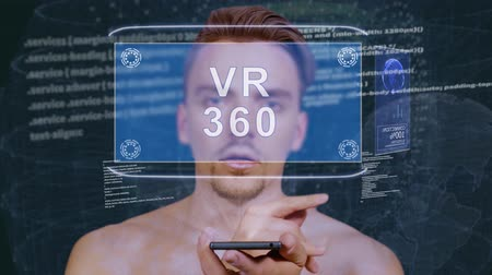 grãos : Young man interacts with a conceptual HUD hologram with text VR 360. Guy with future technology mobile screen on background of the program code