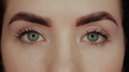 bizakodó : Beautiful girl with green eyes close-up. Young woman opens her eyes and looks straight into the frame