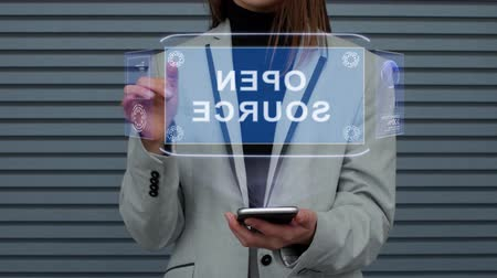 aplikace : Unrecognizable business woman, interacts with a HUD hologram with text Open source. Girl in a business suit uses the technology of the future mobile screen against the background of a striped wall