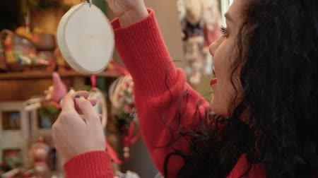 киоск : The girl in the red sweater chooses Christmas toys. Young curly woman looks at the Christmas toys and decorations in a shop window during the Christmas season in winter Стоковые видеозаписи