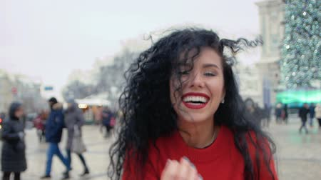 ветреный : Cute girl blowing in the frame warm air against the backdrop of the winter city square. Closeup portrait of a young woman smiling with black curly hair. Slow motion Стоковые видеозаписи