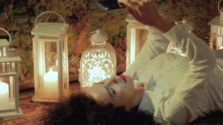 пламя : Girl with a mobile phone on the floor. Young curly woman in white with beautiful red lips is lying on the carpet, against the background of lanterns with candles and uses the app in the smartphone