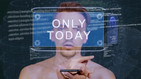 only today : Young man interacts with a conceptual HUD hologram with text Only today. Guy with future technology mobile screen on background of the program code