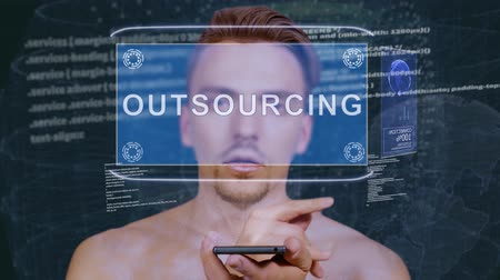 externalisation : Young man interacts with a conceptual HUD hologram with text Outsourcing. Guy with future technology mobile screen on background of the program code
