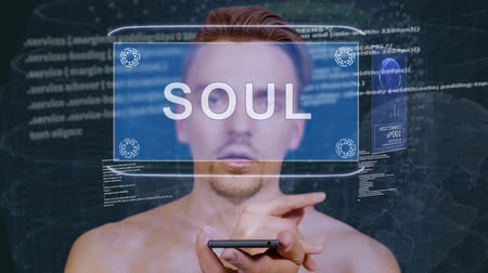 duše : Young man interacts with a conceptual HUD hologram with text Soul. Guy with future technology mobile screen on background of the program code Dostupné videozáznamy