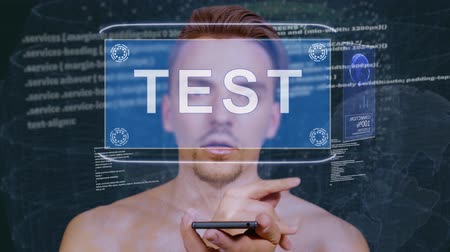 cite : Young man interacts with a conceptual HUD hologram with text Test. Guy with future technology mobile screen on background of the program code Stock Footage