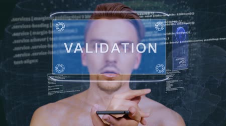 auditing : Young man interacts with a conceptual HUD hologram with text Validation. Guy with future technology mobile screen on background of the program code