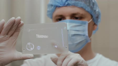tudós : Doctor in mask interacts futuristic hud screen tablet with text Transparency. Medical concept of future technology. Futuristic doctor with modern medical care gadget