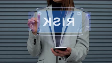 olasılık : Unrecognizable business woman, interacts with a HUD hologram with text Risk. Girl in a business suit uses the technology of the future mobile screen against the background of a striped wall Stok Video