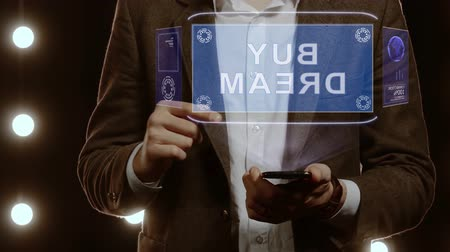árverés : Businessman activates conceptual HUD hologram on smartphone with text Buy dream. Man in a white shirt and jacket with a holographic screen on the background of lights