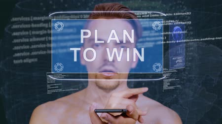 gidermek : Young man interacts with a conceptual HUD hologram with text Plan to win. Guy with future technology mobile screen on background of the program code