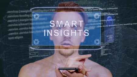 insight : Young man interacts with a conceptual HUD hologram with text Smart insights. Guy with future technology mobile screen on background of the program code Stock Footage
