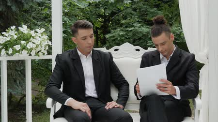dokumenty : Young businessmen sign a contract on a luxurious armchair in a white arbor. Entrepreneur and businessman talk, draw up a contract, sign documents, draw up a deal, shake hands