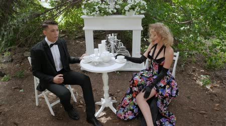 pěvec : Romantic couple man and woman sitting at the table in the forest. A loving couple drinking coffee in a cafe and singing. Duet of singers sing sensually on the background of white furniture in nature