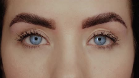 umutlu : Beautiful girl with blue eyes close-up. Young woman opens her eyes and looks straight into the frame Stok Video