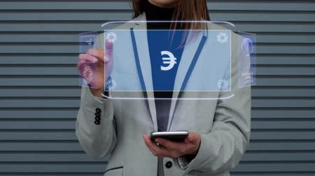 eur : Unrecognizable business woman, interacts with a HUD hologram with text Sign EUR. Girl in a business suit uses the technology of the future mobile screen against the background of a striped wall