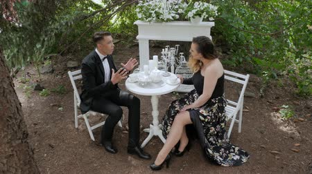 divorzio : Couple in love, swears in a summer cafe. Couple man and woman arguing at a table in the forest. Duet of singers sing sensually on the background of white furniture in nature Filmati Stock