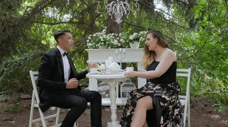 reconcile : Couple man and woman argue and reconcile. Couple in love, swears in a summer cafe. Duet of singers sing sensually on the background of white furniture in nature