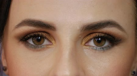 bizakodó : A young woman looks straight into the frame and closes her eyes. Beautiful girl with brown eyes close-up