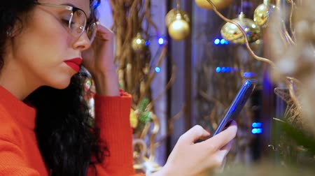 elküldés : Young smiling curly woman in glasses, a red sweater and with red lips with a phone on a background of Christmas decor. Girl holds smartphone on New Years Eve