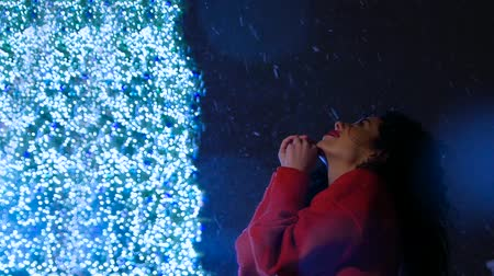 umutlu : Beautiful attractive curly woman in red standing near a New Year tree with garlands peers into the night sky and falling snowflakes. New Year Christmas. Make a wish or pray Stok Video