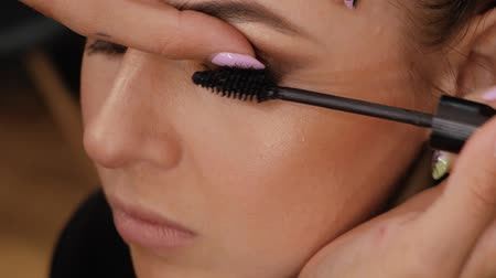 relance : Beautiful brunette uses mascara to make eyelashes brown eyes. Makeup artist professionally applying mascara to client Vídeos