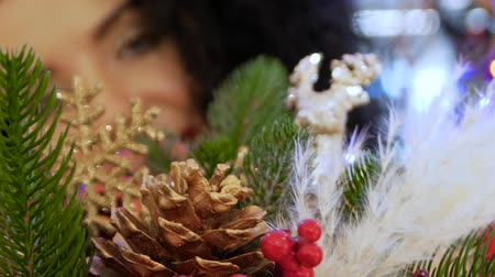 bombki : Unrecognizable young curly woman looks out through Christmas baubles, toys and decorations during the Christmas season. Girl smiles beautifully against the background of New Years attributes