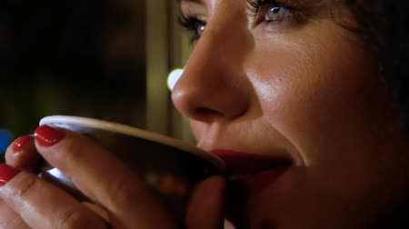 içme : Young woman with a beautiful smile drinks hot coffee from a paper cup, closeup. Female lips take a sip of a hot drink Stok Video