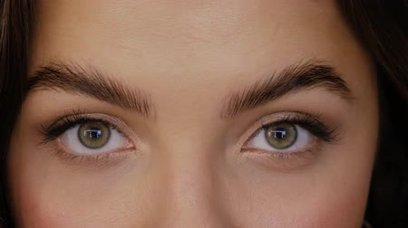 umutlu : A young woman looks straight into the frame and closes her eyes. Beautiful girl with green brown eyes close-up