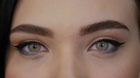 bizakodó : A young woman with professional makeup looks straight into the frame and closes her eyes. Beautiful girl with green brown eyes close-up