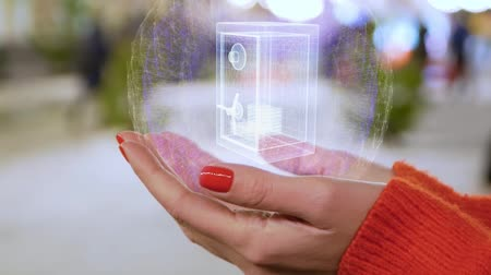 награда : Female hands holding a conceptual hologram with safe with money. Woman with red nails and sweater with future holographic technology on a blurred background of the street