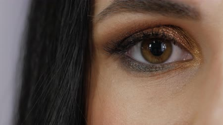 hopeful : Beautiful female brown eye close-up. Young woman opens her eye and looks straight into the frame