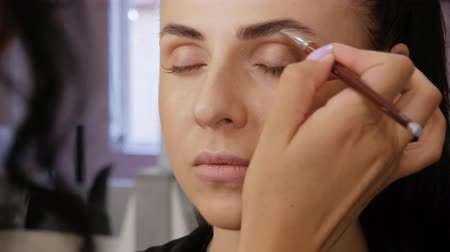 contornos : Professional makeup artist draws eyebrows with a special eyebrow brush of a beautiful girl. Client woman in beauty salon doing eyebrows makeup close-up