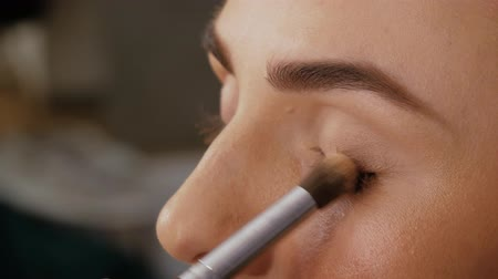 contornos : Close-up in beauty salon. Hand of a professional makeup artist applies a brush to the upper eyelid of a beautiful girl with a brush. Client woman in beauty salon doing makeup